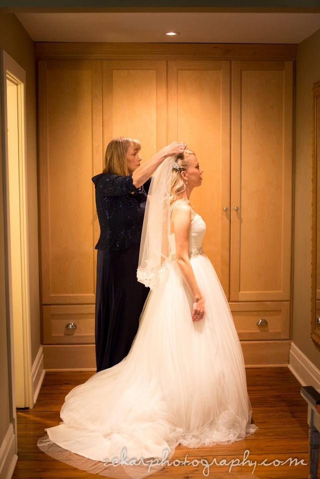 mom putting veil on bride