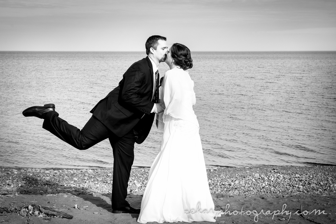 black and white photo of groom and bride kissing