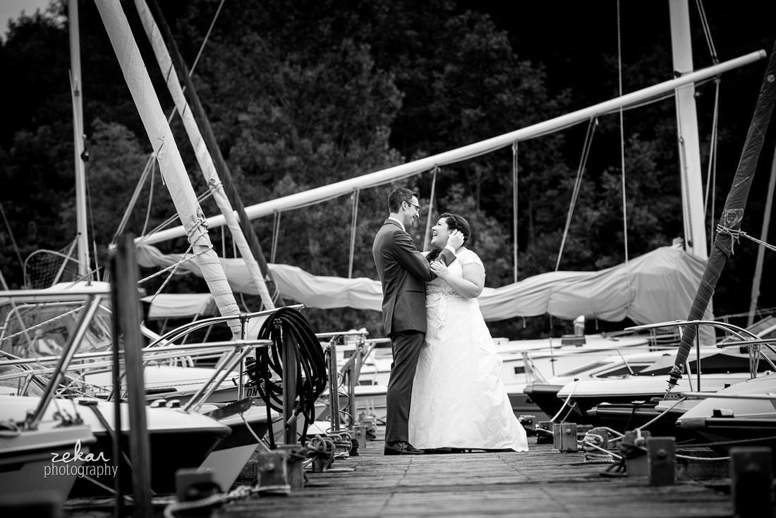bride and groom laughing on boat dock