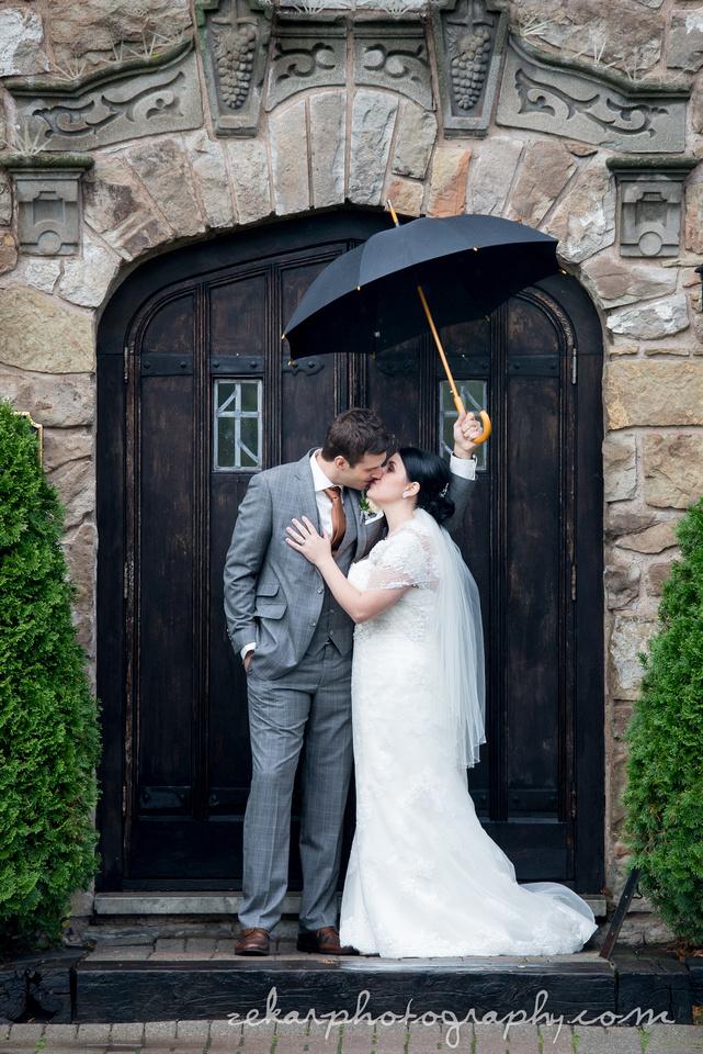 handsome wdding couple kissing under umbrella