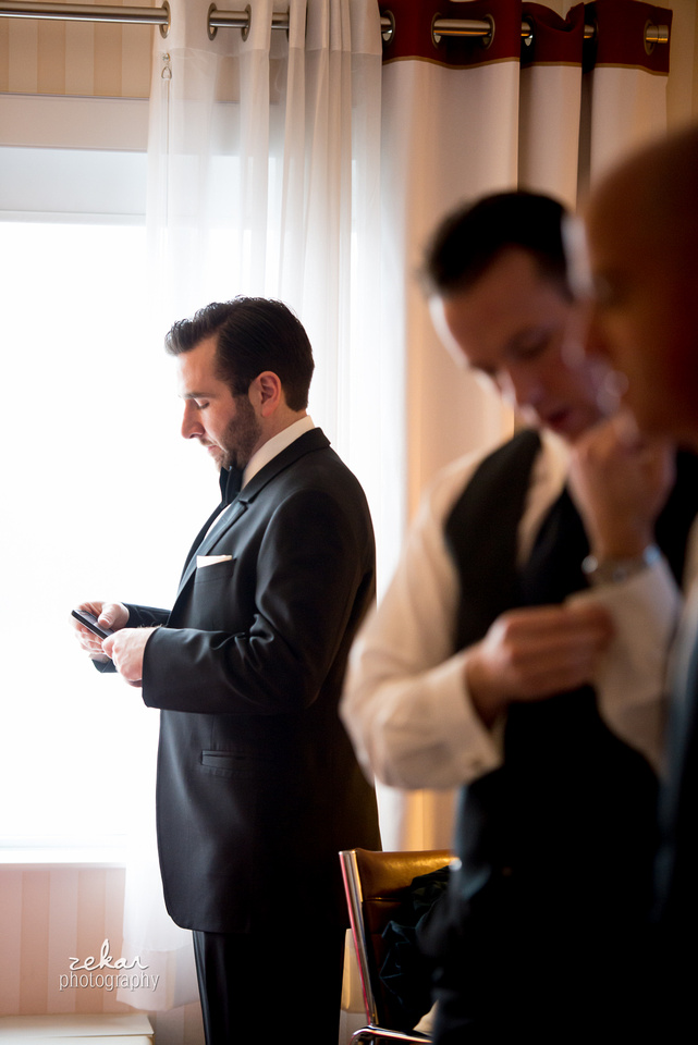 groom looking at cell phone