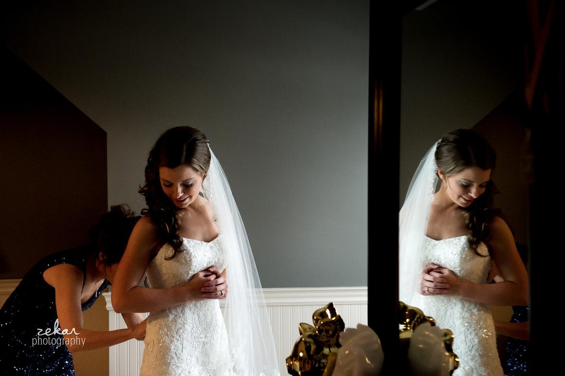 bridesmaid doing up bridal dress