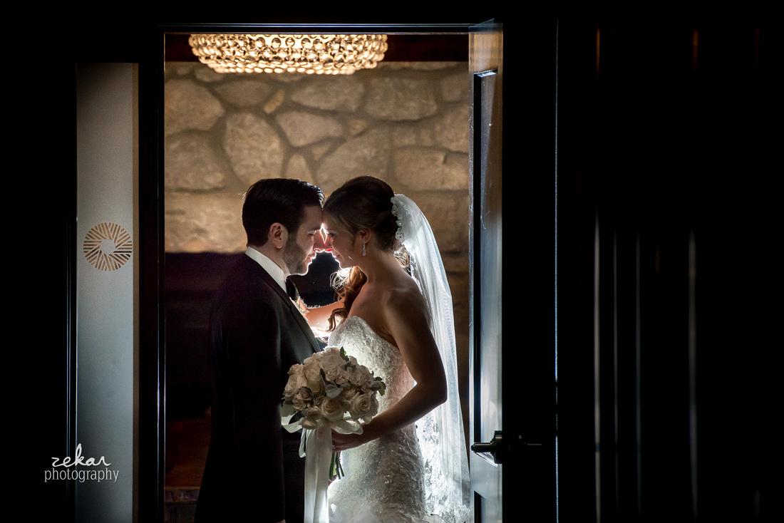 bride and groom posing in doorway backlit