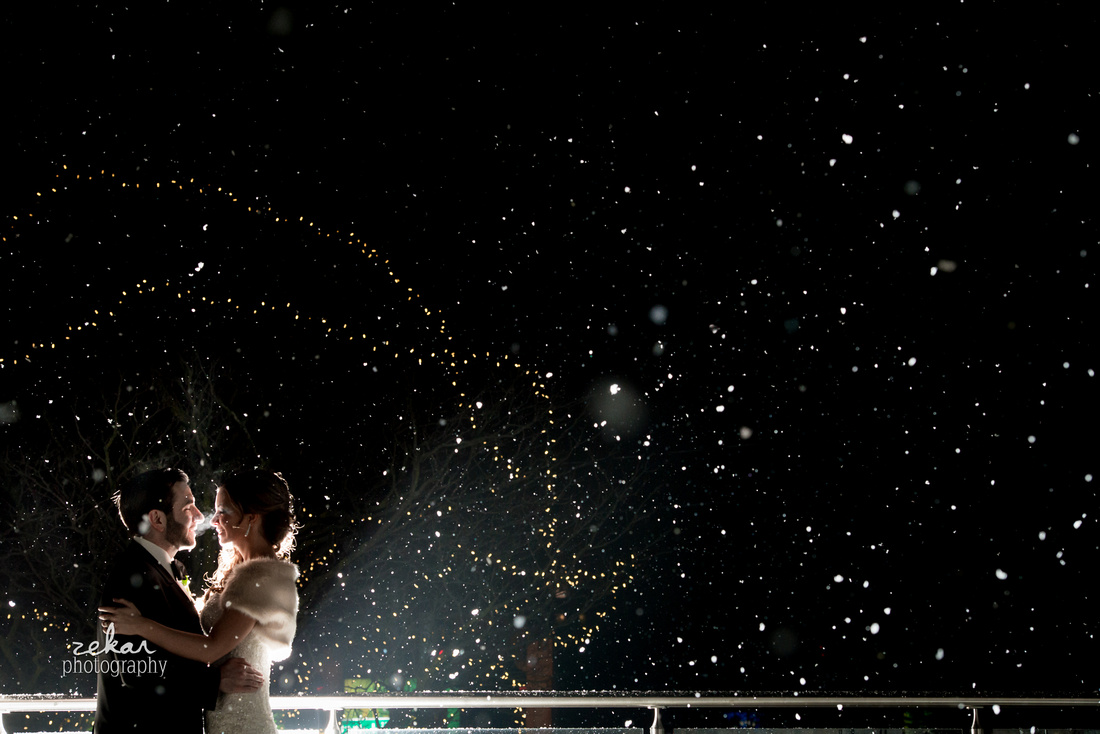 bride and groom kissing in snowstorm