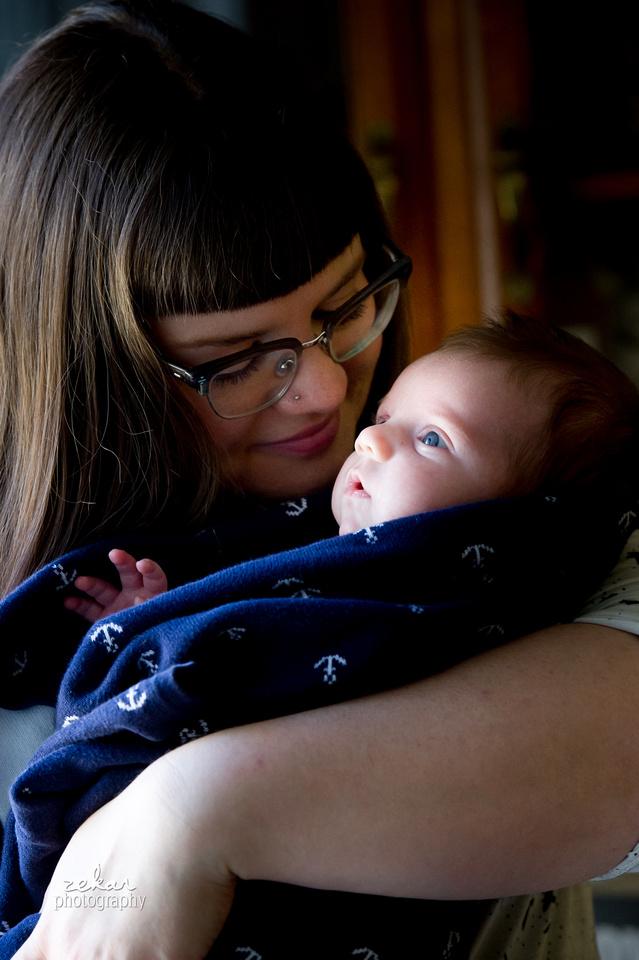 new mom snuggling with newborn baby family documentary photoshoot
