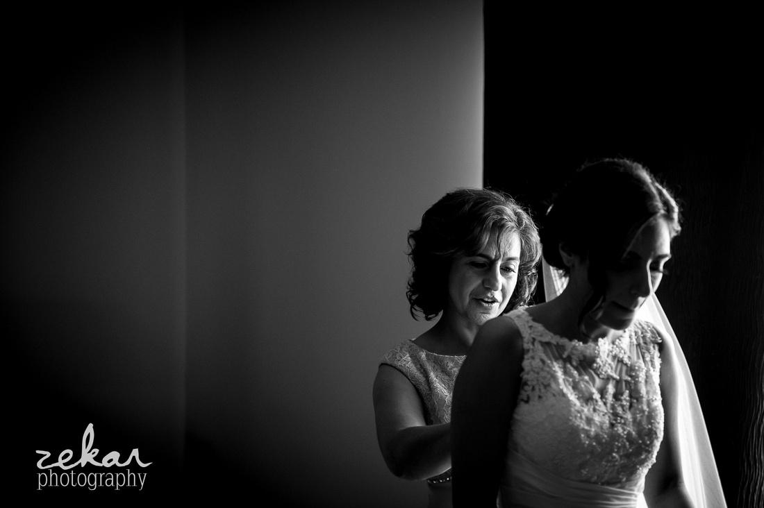 mother doing up wedding dress