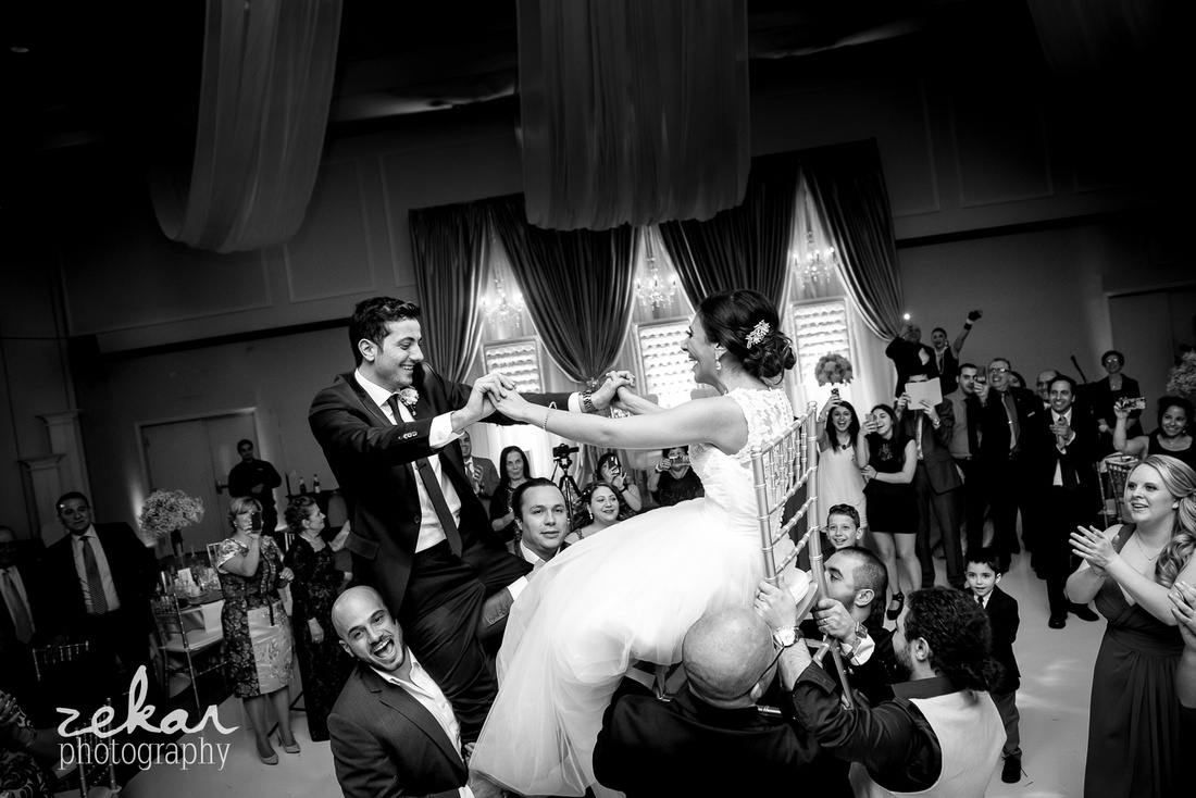 bridal party lifts bride and groom up on chairs