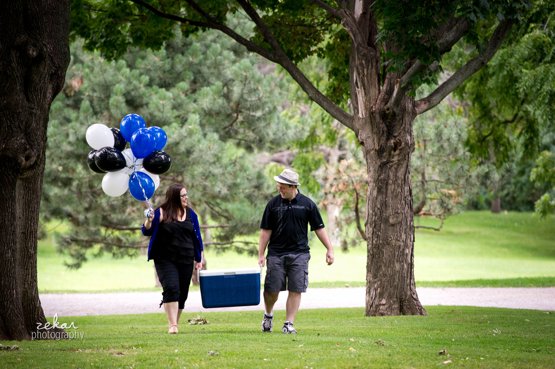 couple walking with cooler and blue black and white balloons