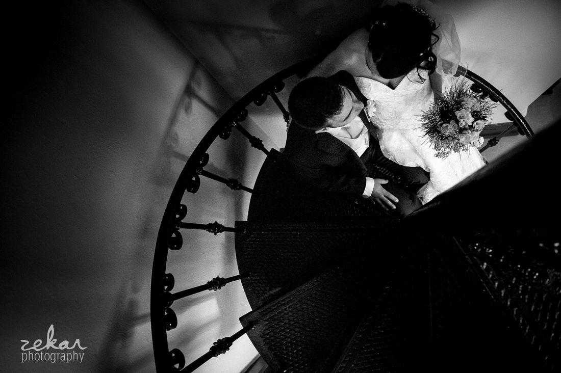wedding couple snuggling on metal spiral stairs