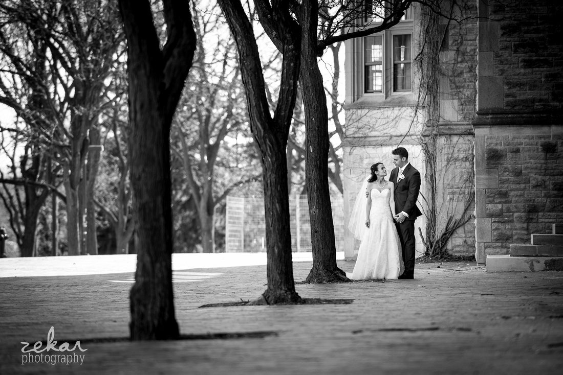 bride and groom walking through trees holding hands