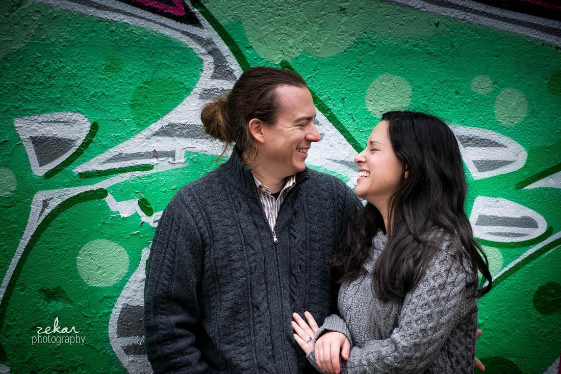 couple laughing near graffiti