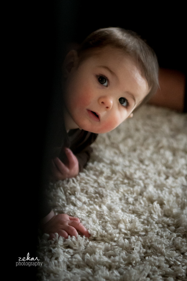 little baby peeking behind couch