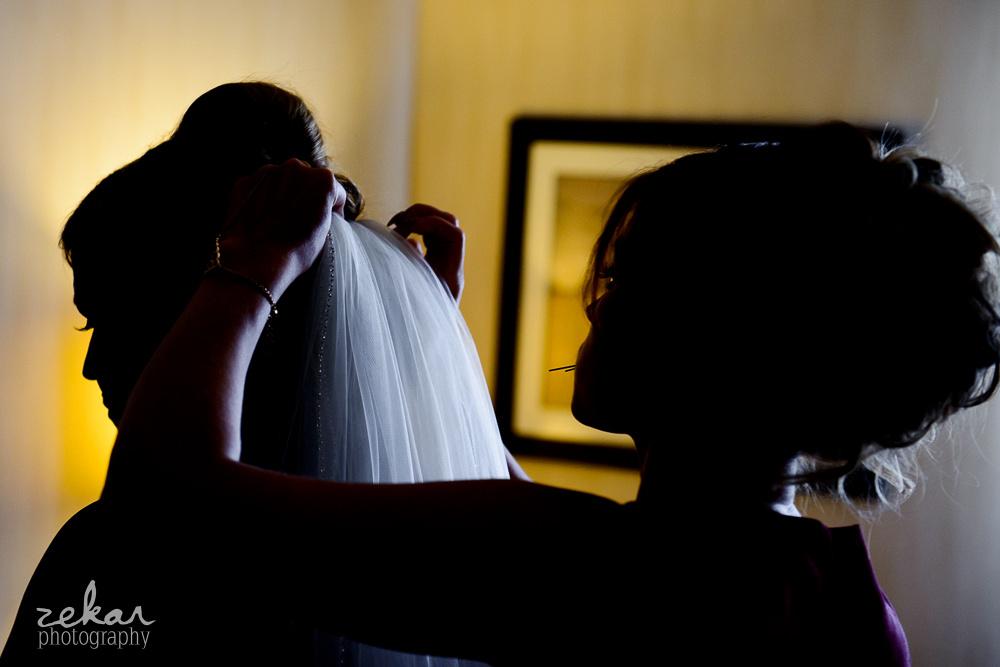 bridesmaid putting on veil on wedding day