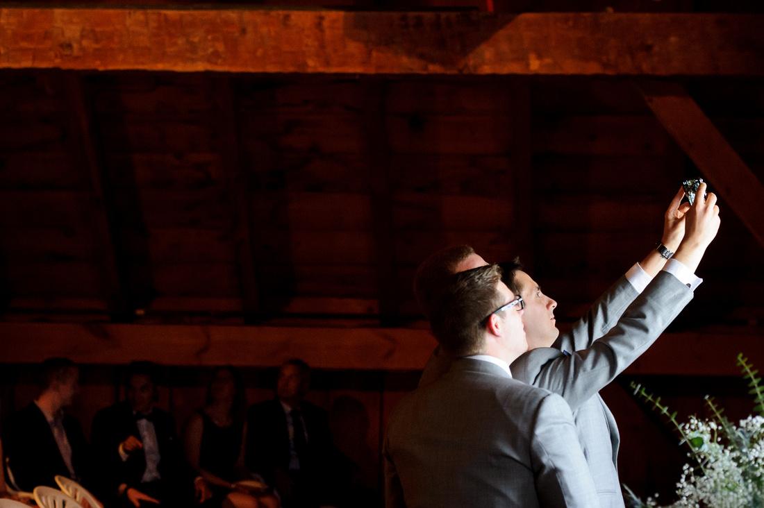 groomsmen taking selfie at altar