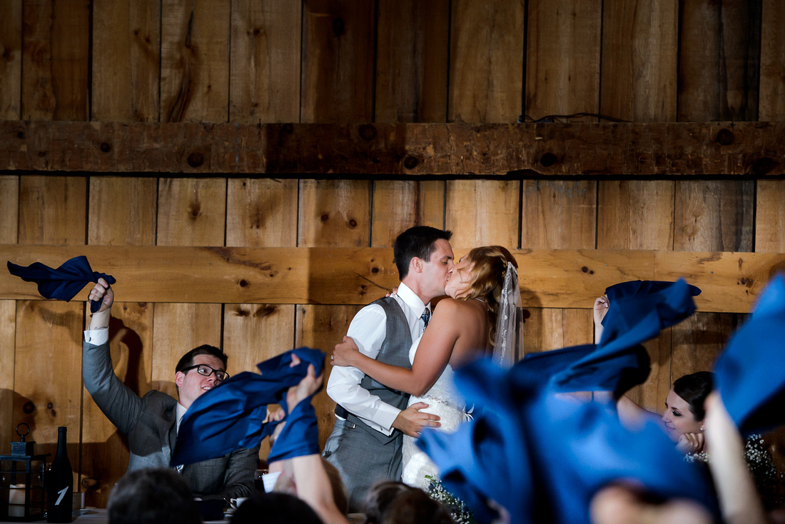 bride and groom kissing with blue napkins