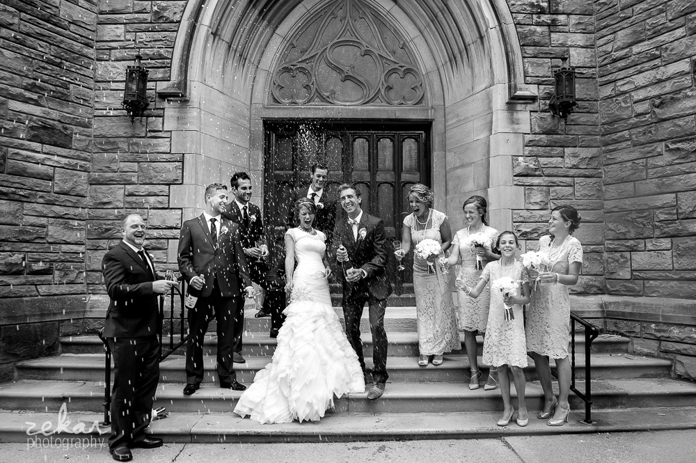 groom spraying bridal party with champagne