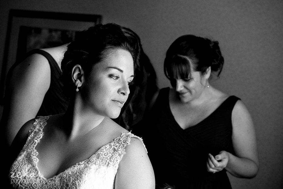 bride looking at friends doing up dress