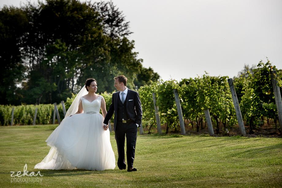 wedding couple walking through field
