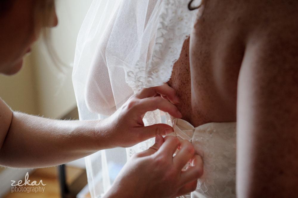 hands doing up bride dress