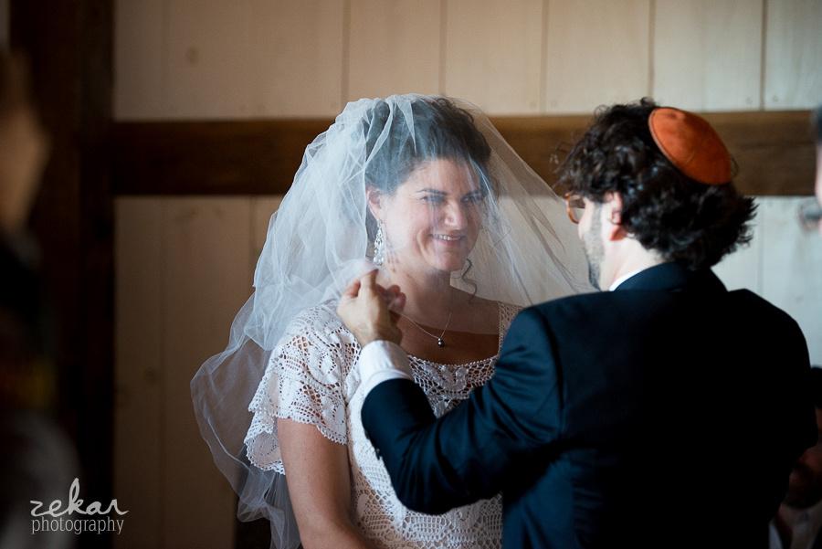 groom putting veil on