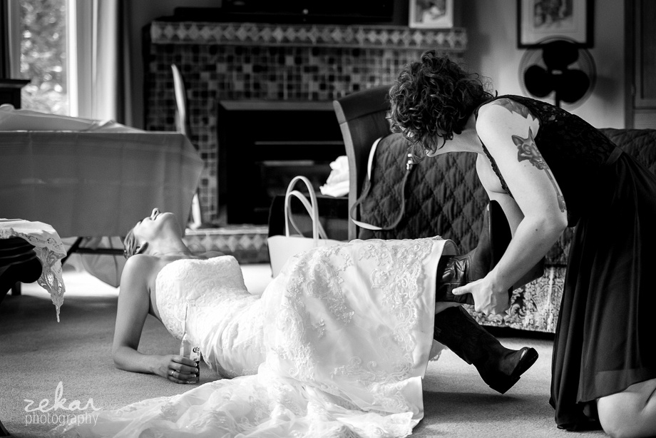 bride laughing as boots are shoved on