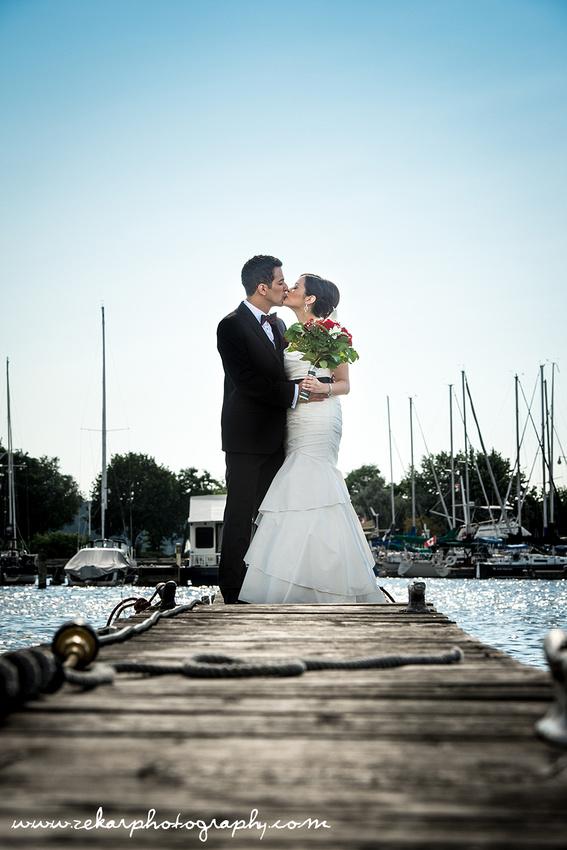 hamilton wedding zekar photography bride and groom kissing on dock at marina
