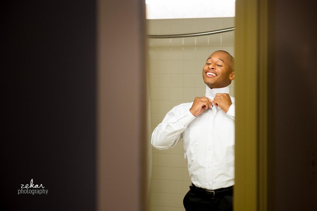 groom laughing putting tie on