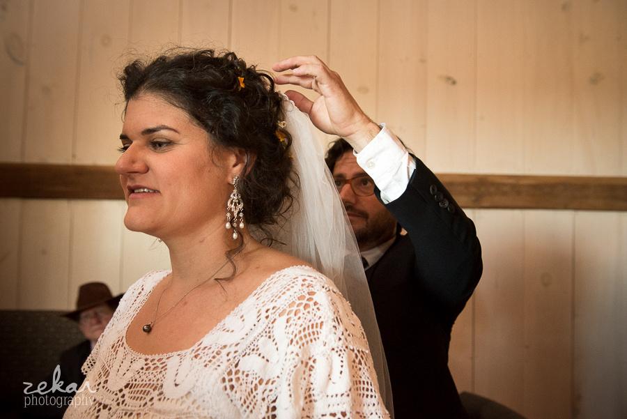groom putting bride veil on