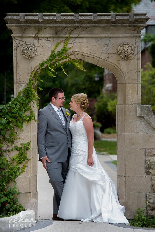 bridal couple under stone archway