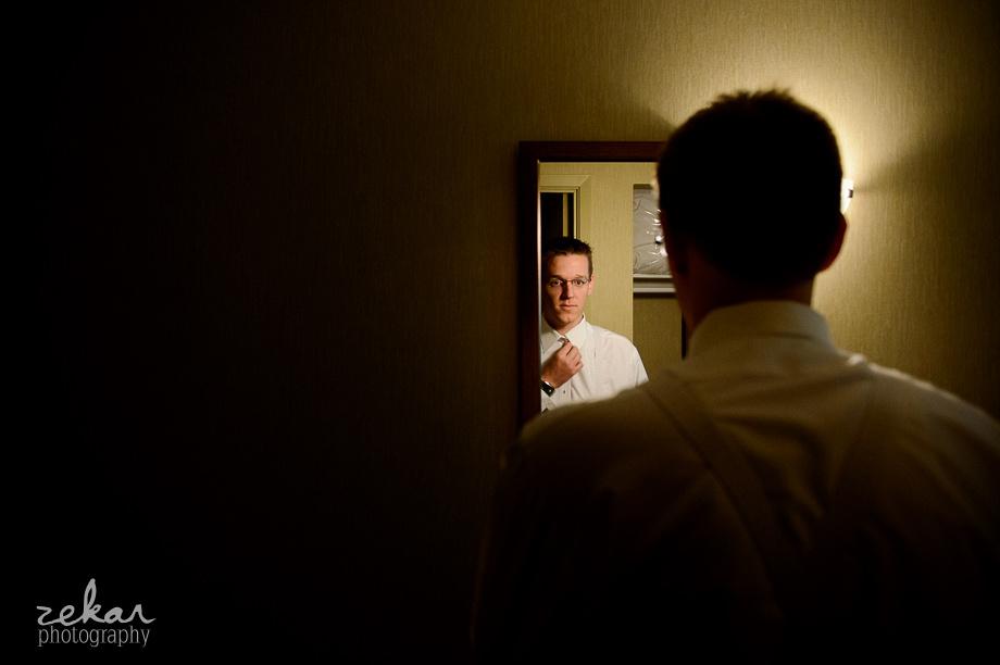 groom putting tie on in mirror