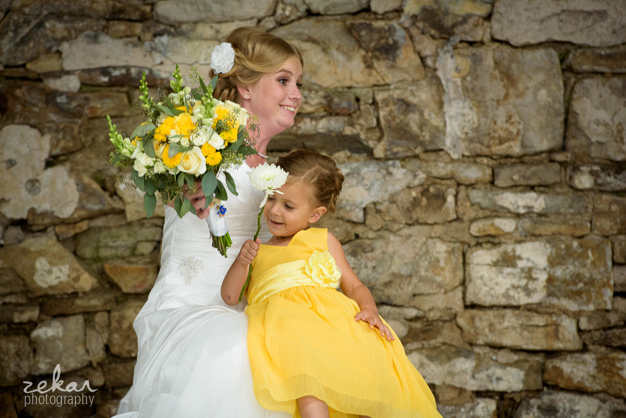 bride and flower girl snuggling then falling