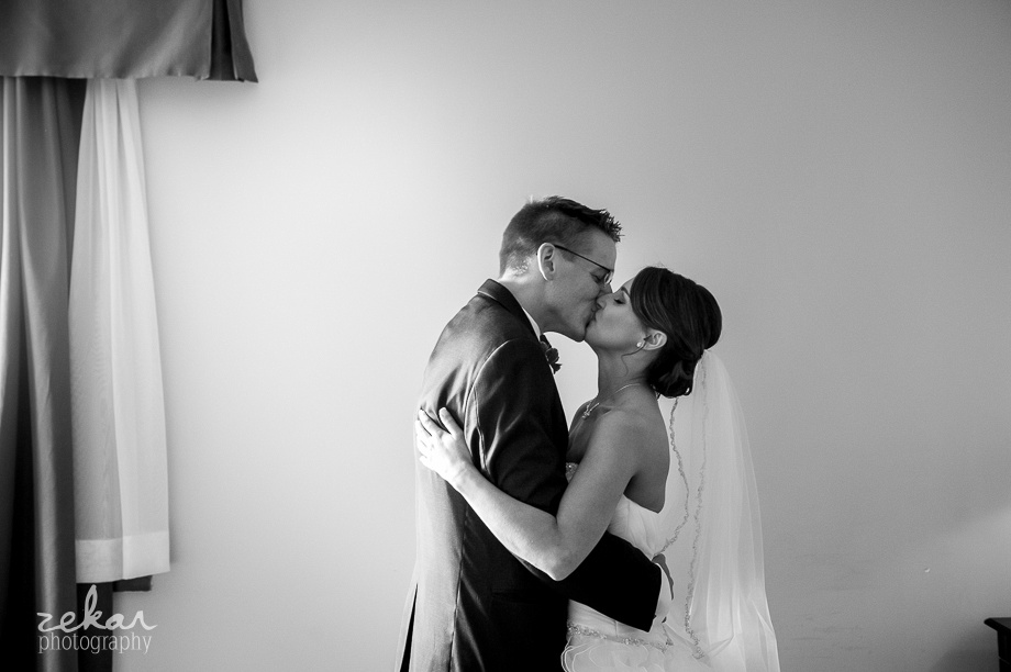 groom and bride kissing in hotel room