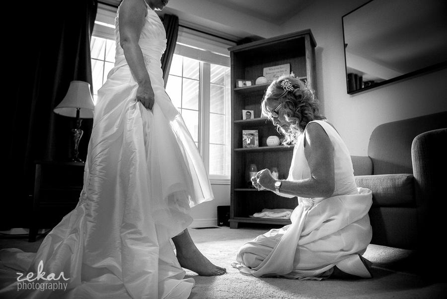 mom putting anklet on bride