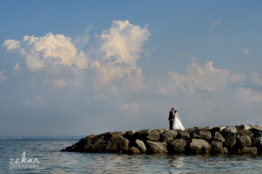 bride and groom on rocks on water
