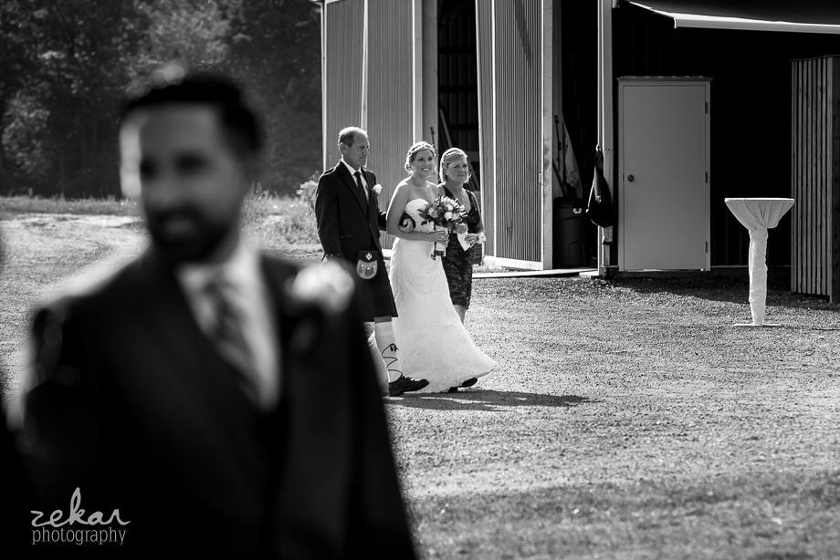 bride walking behind groom aisle