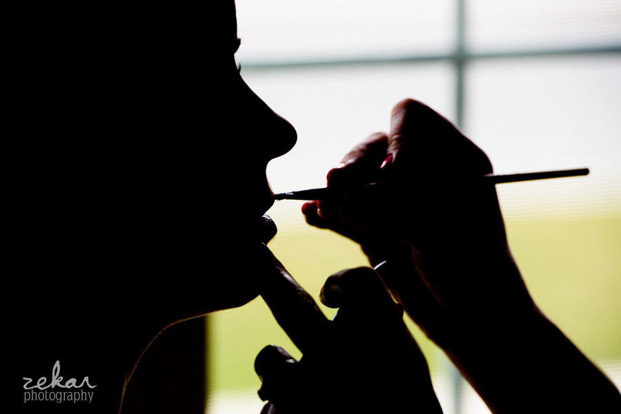 silhouette of bride getting lipstick on