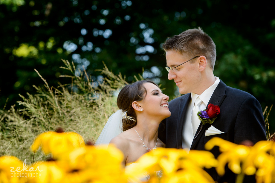 couple smiling at eachother behind yellow flowers