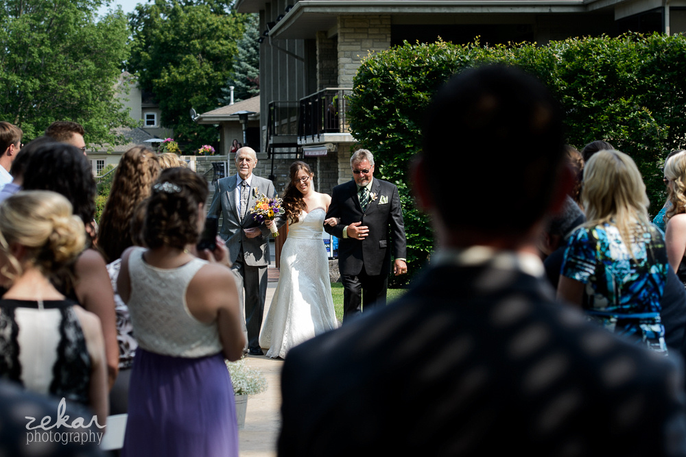 bride walking down aisle with grandpa and dad