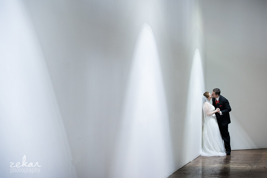 bride and groom kissing against wall