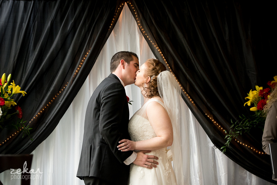 bride and groom kissing altar