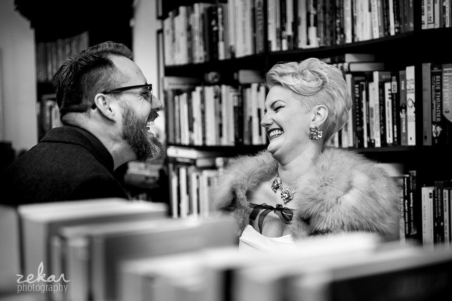 bride and groom laughing in books