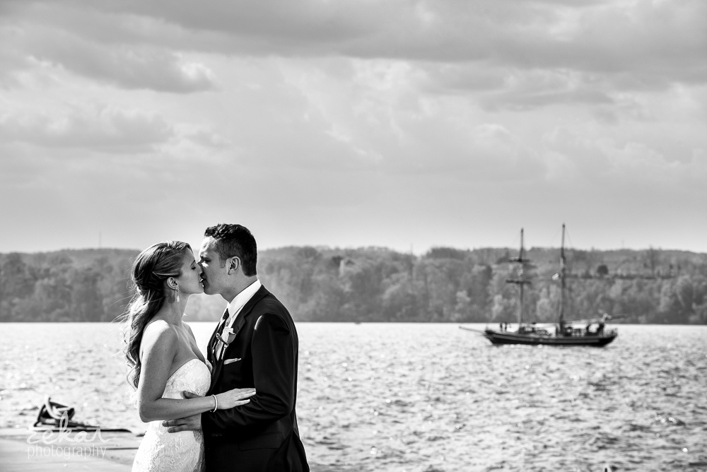 bride and groom kissing by ship