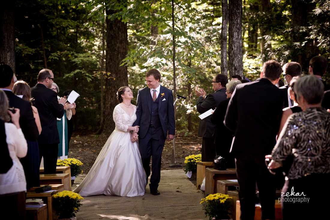 bride and groom smiling down wedding aisle