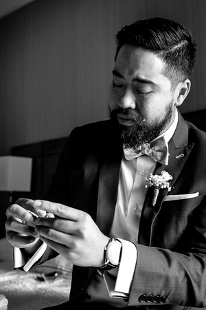 Groom crying over gift. Black and white. wedding photojournalism.