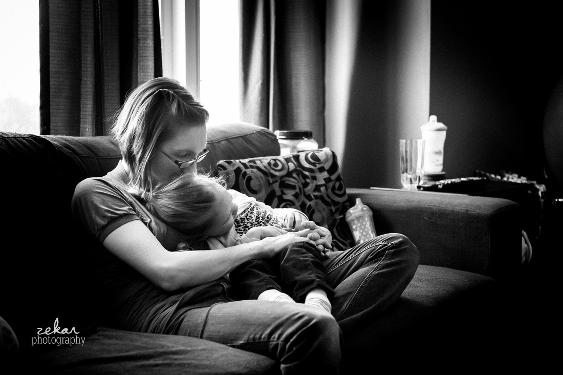mom snuggling little girl on couch