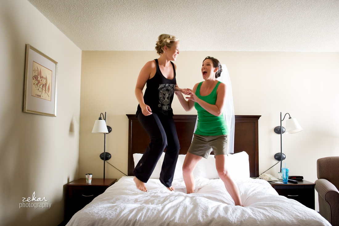 bride and bridesmaid jumping on bed