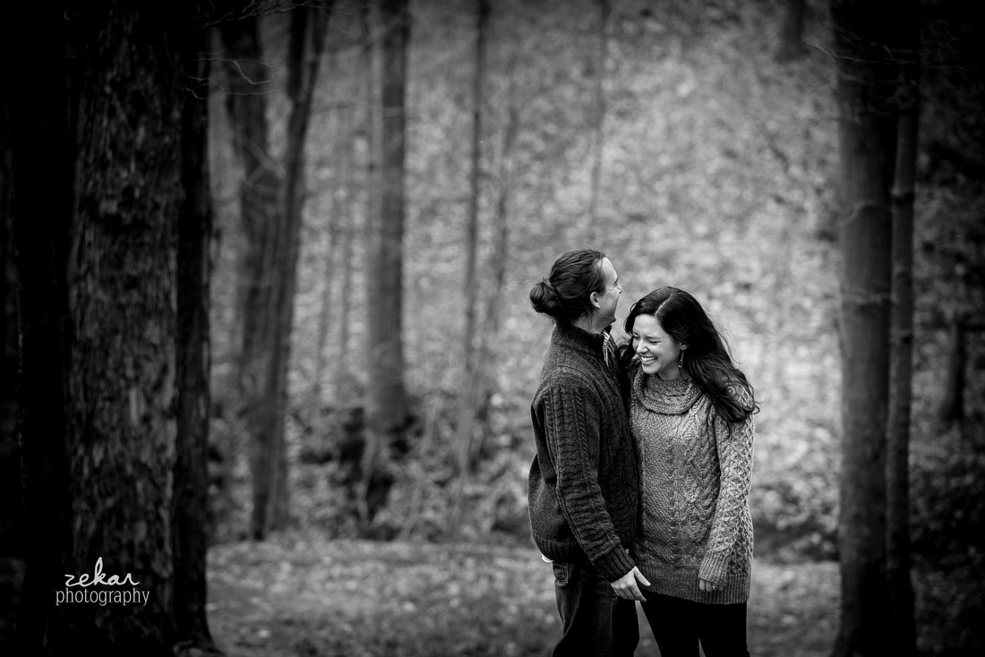 couple laughing in fall leaves