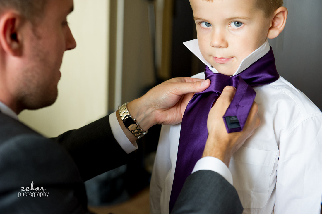 man putting tie on little boy
