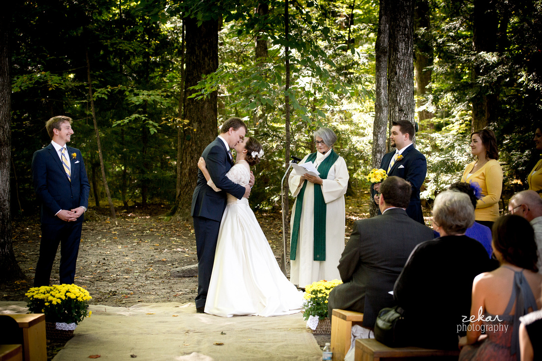bride and groom kissing woods altar