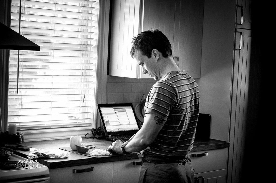 dad making dinner with laptop in background